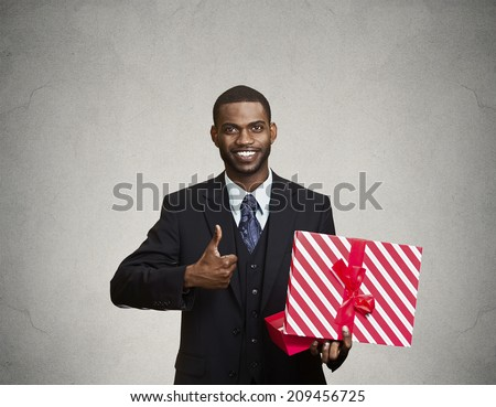 Portrait young happy, smiling business man holding present, red gift box, giving thumb up isolated grey wall background. Positive facial expressions, human emotions, body language, life perception - stock photo