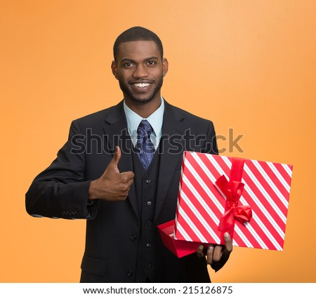 Portrait young happy, smiling business man holding present, red gift box, giving thumb up isolated orange background. Positive facial expression, human emotion body language, life perception attitude  - stock photo