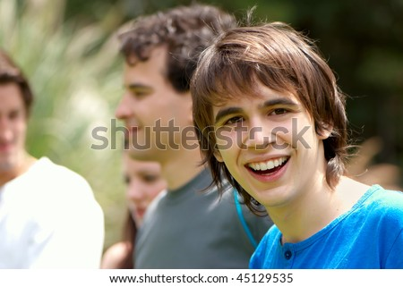 Portrait young happy teenage boy at the park with friends - stock photo