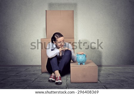 Portrait young happy woman sitting on the floor with many boxes, moving out