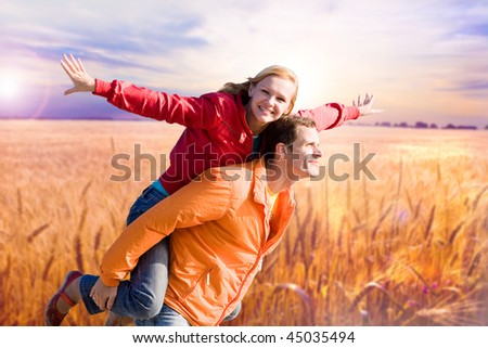 Portrait Young love Couple smiling under Golden wheat ready for harvest growing - stock photo