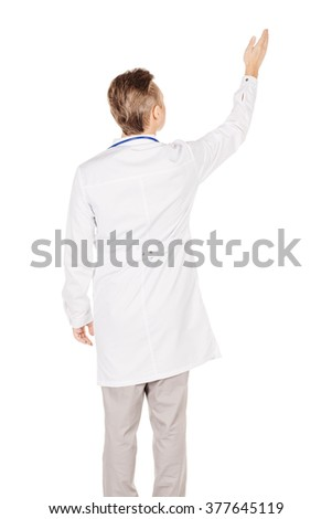 Portrait young male doctor in white coat directional pointing at distance looking away. People and medicine concept. Image isolated on a white background. - stock photo