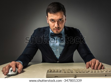 Portrait young man in blue shirt and jacket looking at the camera,  sitting at a desk near a computer isolated on gray studio background. Human emotion, facial expression. Closeup