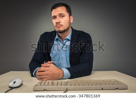 Portrait young man in blue shirt and jacket looking at the camera, sitting at a desk near a computer isolated on gray studio background. Human emotion, facial expression. Closeup - stock photo