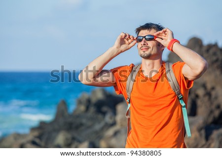 portrait young man in glasses with backpack. Backround sea - stock photo