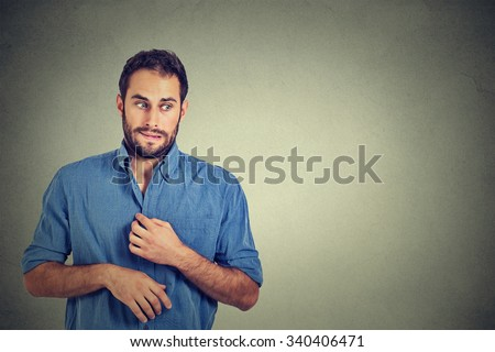 Portrait young man opening shirt to vent, it's hot, unpleasant, awkward situation, playing nervously with hands. Embarrassment. Isolated gray background. Negative emotions facial expression feeling - stock photo