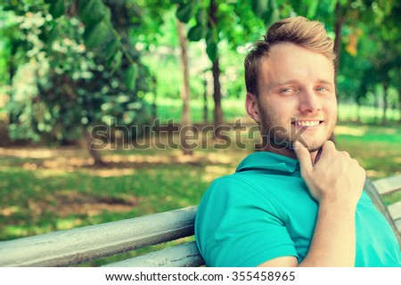 Portrait young man outdoors with park background copy space - stock photo