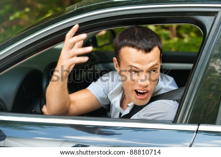 Portrait young man sitting car looking out window looks back indignantly background summer green park - stock photo