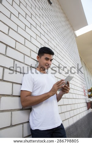 Portrait young man using electronic tablet happy on wall.