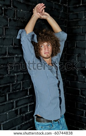 Portrait young man with a curly hair against a black wall - stock photo