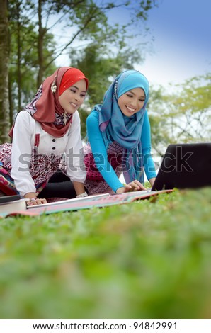 Portrait young muslim women relaxed and happy at the park with laptop - stock photo