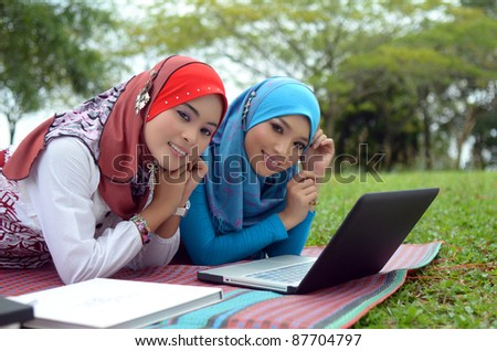 Portrait young muslim women relaxed at the park   with laptop - stock photo