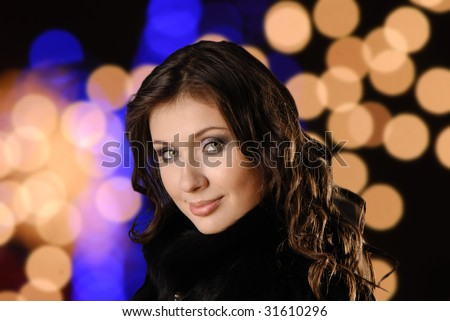 Portrait  young nice woman with  dismissed hair on  background of illumination