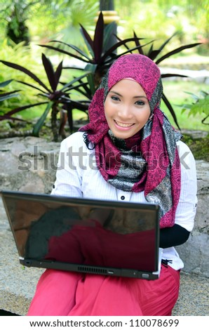 Portrait young pretty Asian muslim businesswomen with laptop and smile