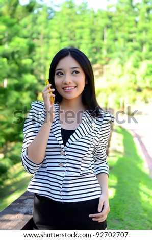 Portrait young pretty Asian muslim college girl with mobile phone - stock photo