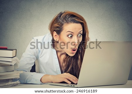 Portrait young shocked business woman sitting in front of laptop computer looking at screen isolated grey wall background. Funny face expression emotion feelings problem perception reaction  - stock photo