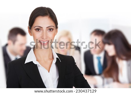 Portrait young smiling businesswoman against team discussing in boardroom - stock photo