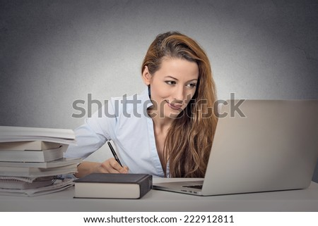 Portrait young student studying hard working on computer taking notes surrounded by books on grey wall background. Positive human face expressions - stock photo
