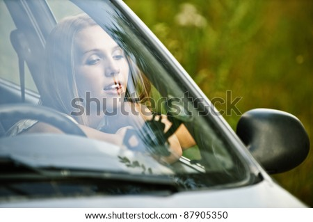 portrait young thoughtful beautiful woman sitting car leaned open window dreams background summer green nature - stock photo