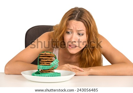 Portrait young unhappy woman craving sugar sweet cookies but worried about weight gain sitting at table isolated on white background. Human face expression emotion. Diet nutrition dilemma concept - stock photo