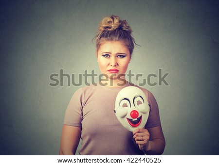 Portrait young upset worried woman with sad expression holding a clown mask expressing cheerfulness happiness isolated on gray wall background. Human emotions  - stock photo