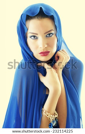 Portrait young woman covered with fabric over head - High Key studio shot - stock photo