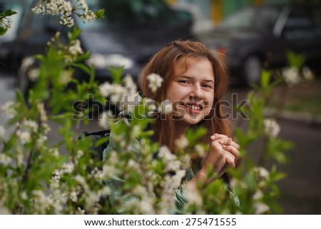 Portrait young woman in a wheelchair outside in spring day - stock photo