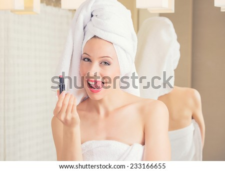 Portrait young woman in hotel bathroom smiling with towel on her head after bath refreshing herself applying makeup. Positive face expression emotion feeling. Healthy life wellness happiness concept  - stock photo