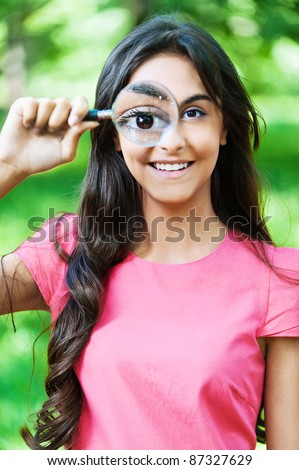 portrait young woman long hair looking through magnifying glass - stock photo