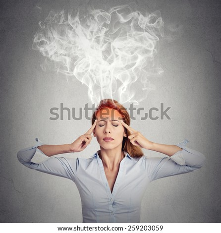 Portrait young woman thinking too hard steam coming out up of head isolated on grey wall background. Face expression emotion perception  - stock photo