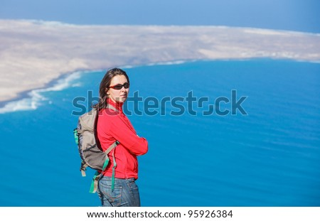 Portrait young woman with backpack looking to the island. - stock photo