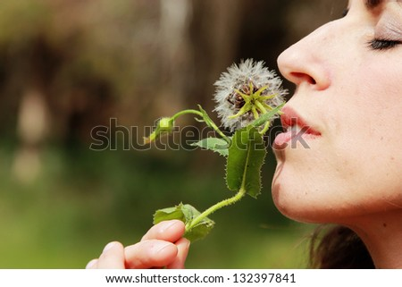 portrait young woman with dandelion - stock photo