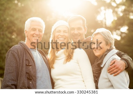 Portraitr of a smiling family on an autumns day - stock photo