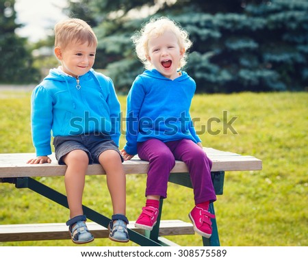 Portraits of Caucasian cute boy and girl friends laughing talking hugging outside in park on summer day, backlit with sun from behind, rim light of figures - stock photo