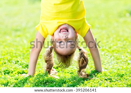 Portraits of happy kid playing upside down outdoors in summertime standing on hands on grass - stock photo