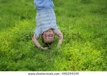 Portraits of happy kids playing upside down outdoors in summer park walking on hands in grass. Adorable little boy hanging upside down having fun outdoors summertime. practice capoeira dance acrobatic - stock photo