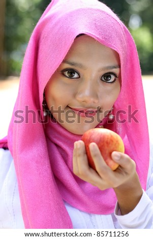 Portraits of muslim woman with an apple - stock photo