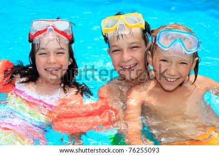 Portraits of three happy children with swimming goggles in a swimming pool. - stock photo