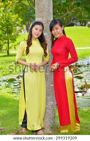 Portraits of two pretty girls wearing Ao Dai (Vietnam nation dress) in park