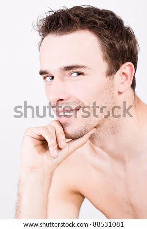 portraiture of attractive smiling man, young handsome male model - made in studio on white background - stock photo