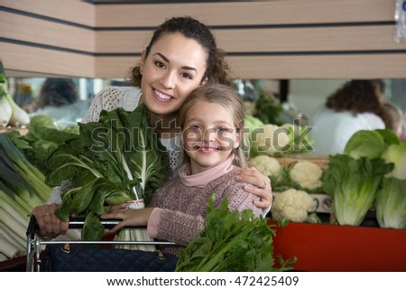 portret of young smiling woman with beautiful blonde daughter choosing green vegetables at store