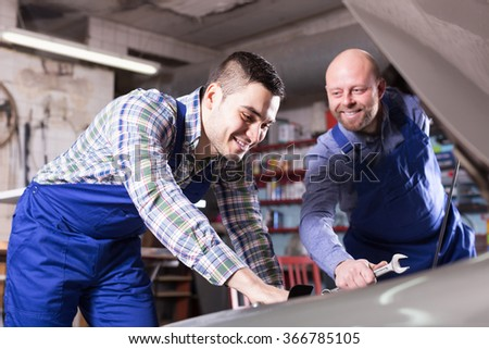 Portret to professional adult smiling mechanics repairing car of client - stock photo