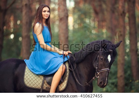 Portriat of smiling young beautiful brunette girl in blue dress ride on the black horse in forest - stock photo