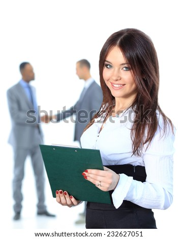Portrrait of a smiling young business woman with people discussing in background - stock photo