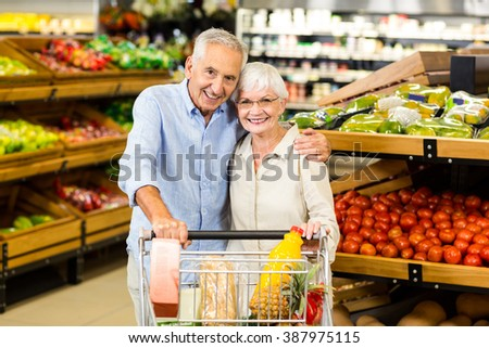 Portrsit of happy senior couple with cart at the grocery shop - stock photo