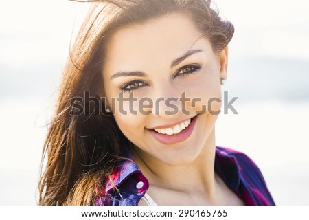 Portrtait of a happy girl at the beach smilling  - stock photo