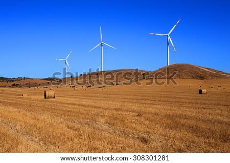 Portugal, Alentejo Region, Wind power turbines in an autumn crop field against a deep blue sky. - stock photo