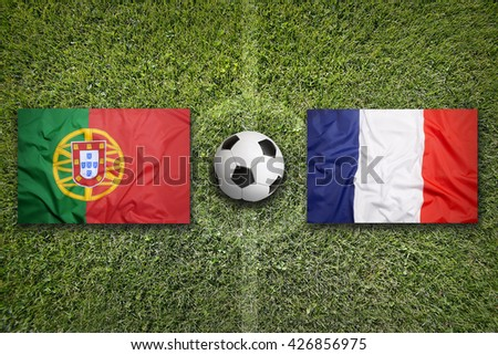 Portugal vs. France flags on a green soccer field - stock photo