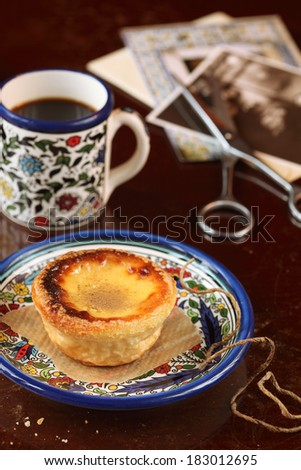 Portuguese Custard Tart and a cup of coffee, on a dark background. - stock photo