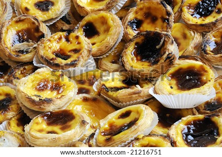 Portuguese Custard Tarts (Pastel de Nata or de Belem). A close-up of traditional Portuguese custard pastries: custard in a creme brulee-like consistency caramelized fashion in a puff pastry case. - stock photo